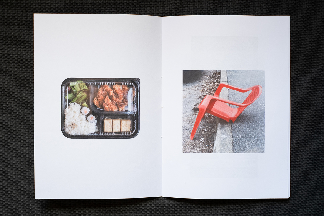 Photograph of a homemade Zine about April 2021, photographed on a dark grey background. Shown here is a double page spread with photographs of a tonkatsu bento to the left and a broken red plastic garden chair on a curb to the right.