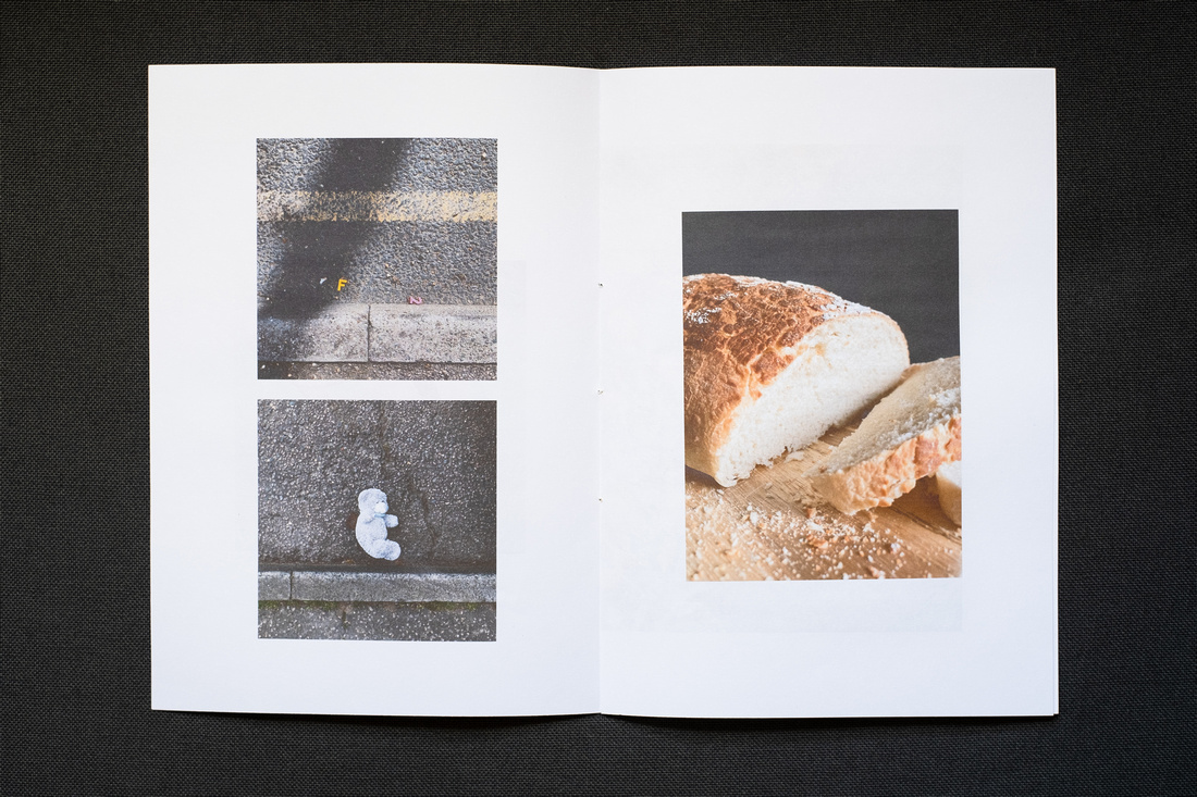 Photograph of a homemade Zine about April 2021, photographed on a dark grey background. Shown here is a double page spread with photographs of fridge magnets in the gutter to the top left, a teddy bear in the gutter to bottom left and a tiger loaf with a slice cut off to the right.