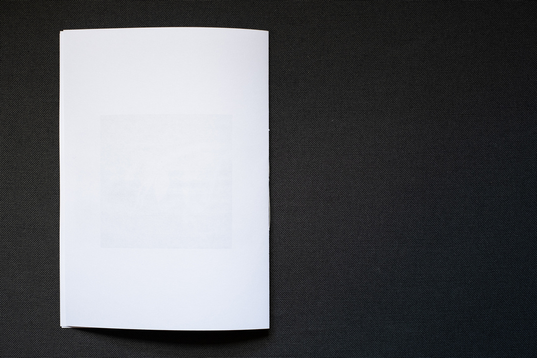 Photograph of a homemade Zine about April 2021, photographed on a dark grey background, showing the blank back page.