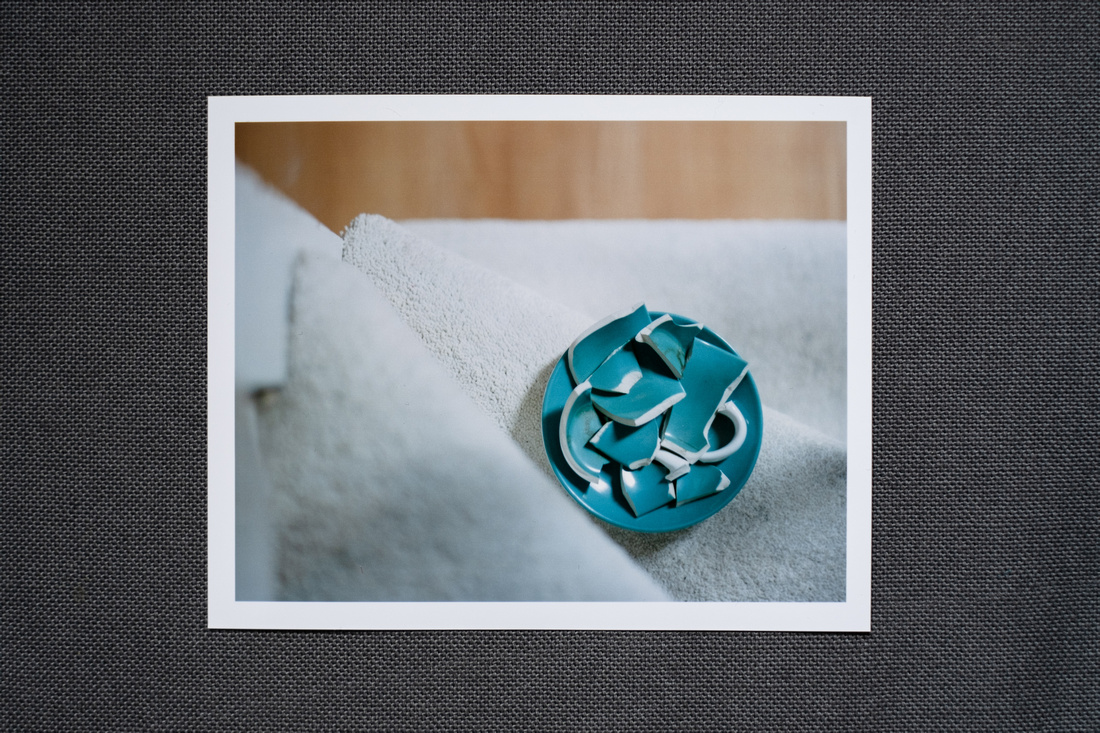 Photographic print on a dark grey fabric background. The photograph shows a broken blue coffee cup on a saucer on a carpeted stair, taken from above.