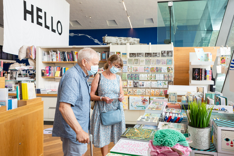 The shop at Firstsite, with books and products on display, and visitors wearing facemarks browsing.