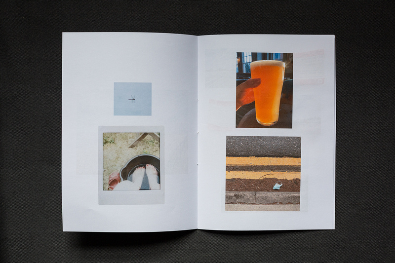 Photograph of a home made photozine on dark grey fabric. Top left image of a dragonfly, an Instax print of feet in a bucket of water below, top right image of a hand holding a pint of beer, and a gutter with a discarded facemark below.