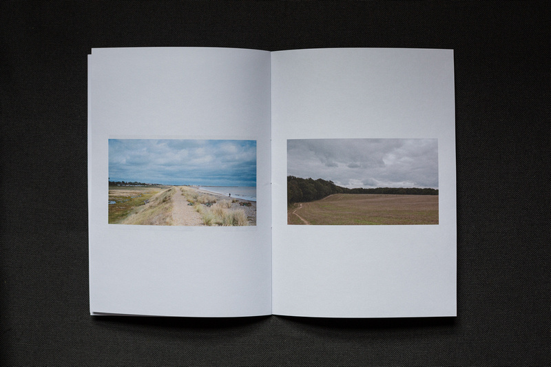 Photograph of a home made photozine on dark grey fabric. On the left hand side an image of a path by the sea on the Dunwich coastline and on the right hand side a field with deer very tiny in the distance.