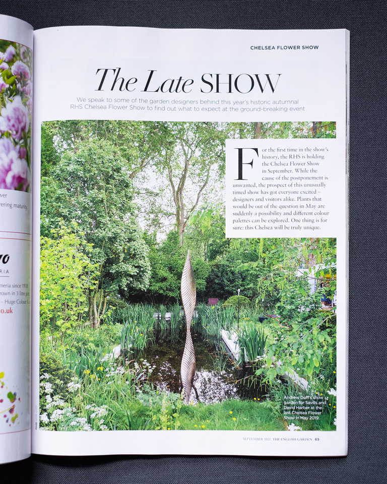 Tearsheet from The English Garden magazine, September 2021 Issue. Photograph shows a page in the magazine showing Andrew Duff's show garden for Savills and David Harber at the May 2019 Chelsea Flower Show with 'The Late SHOW' written at the top and the image itself of a lush garden with a pond featuring a metal sculpture.