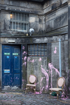 Off Thistle Street, Edinburgh, pink paint splattered all over a wall and 2 cane chairs in the street.